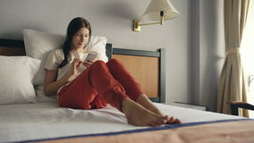 Pretty blonde woman lying in bed in hotel room and use smartphone and smiling stock video footage
