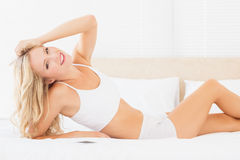 Pretty blonde woman lying on bed smiling at camera Royalty Free Stock Photos
