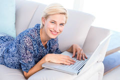 Pretty blonde woman lying on the couch and using her laptop Royalty Free Stock Photo