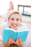 Pretty blonde woman lying on the floor and reading a book Stock Photography