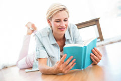 Pretty blonde woman lying on the floor and reading a book Stock Photo
