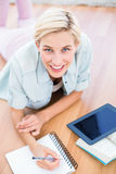 Pretty blonde woman lying on the floor and taking notes while using her tablet Royalty Free Stock Photo