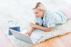 Pretty blonde woman lying on the floor and using her laptop Royalty Free Stock Photography