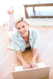 Pretty blonde woman lying on the floor and using her laptop Stock Photography