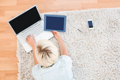 Pretty blonde woman lying on the floor while using her laptop and tablet Royalty Free Stock Image