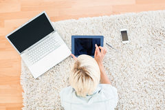 Pretty blonde woman lying on the floor and using her tablet Royalty Free Stock Image