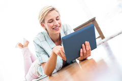 Pretty blonde woman lying on the floor and using her tablet Stock Photo