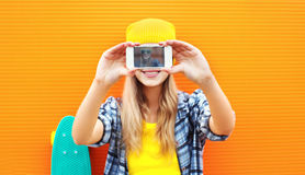 Pretty blonde woman makes self-portrait on smartphone over colorful Stock Photography