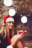 Pretty blonde woman near fireplace with cup of coffee with marsh stock photo