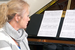 Pretty Blonde Woman At The Piano Royalty Free Stock Image