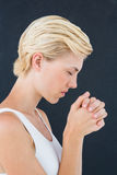 Pretty blonde woman praying Stock Photo