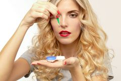 Beautiful blond woman with contact lenses box. Pretty blonde woman pulls out a tweezers contact lens from the box royalty free stock images
