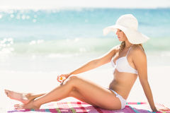 Pretty blonde woman putting sun tan lotion on her leg Royalty Free Stock Images
