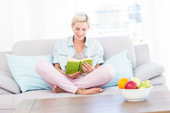 Pretty blonde woman reading a book on the couch Stock Photos