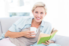 Pretty blonde woman reading a book and holding a mug Stock Photos