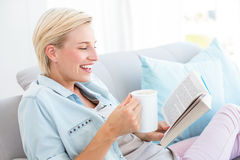 Pretty blonde woman reading a book and holding a mug Stock Photography