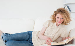 Pretty blonde woman reading a book while lying. On a sofa in her appartment Stock Image