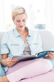 Pretty blonde woman reading a magazine on the couch Stock Photos