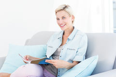 Pretty blonde woman reading a magazine on the couch Royalty Free Stock Photo
