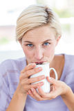Pretty blonde woman relaxing on the couch and holding a mug Stock Images