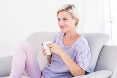 Pretty blonde woman relaxing on the couch and holding a mug Stock Image