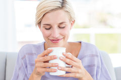Pretty blonde woman relaxing on the couch and holding a mug Royalty Free Stock Photography