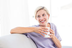 Pretty blonde woman relaxing on the couch and holding a mug Stock Photos