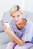 Pretty blonde woman relaxing on the couch and holding a mug Royalty Free Stock Images