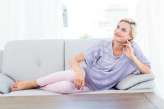 Pretty blonde woman relaxing on the couch Royalty Free Stock Images