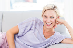 Pretty blonde woman relaxing on the couch and looking at the camera Royalty Free Stock Photo