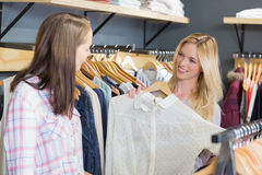 Pretty blonde woman showing clothes to her friend Royalty Free Stock Photography