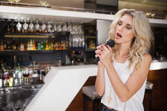 Pretty blonde woman singing while closing her eyes Royalty Free Stock Photos