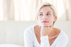 Pretty blonde woman sitting on the bed Stock Photo