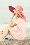 Pretty blonde woman sitting in the sand on the beach. Stock Image