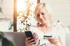 Pretty Blonde Woman Using Credit Card with Phone stock images