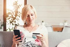 Pretty Blonde Woman Using Credit Card with Phone royalty free stock photos