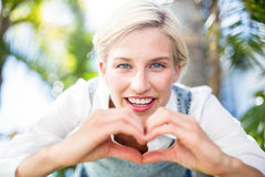 Pretty blonde woman smiling at the camera and doing heart shape with her hands Stock Photography