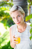 Pretty blonde woman smiling at the camera and drinking orange juice Royalty Free Stock Photo