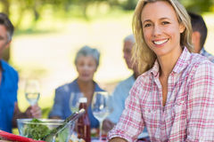 Pretty blonde woman smiling at camera during a picnic Royalty Free Stock Photography
