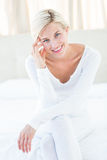 Pretty blonde woman smiling at the camera while sitting on the bed Royalty Free Stock Photos