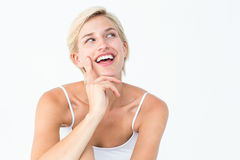 Pretty blonde woman smiling with finger on cheek Royalty Free Stock Photography