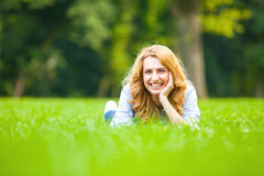 Pretty blonde woman smiling in green grass Stock Photography