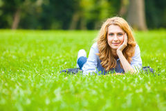 Pretty blonde woman smiling in green grass Royalty Free Stock Photo