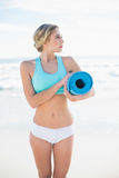 Pretty blonde woman in sportswear carrying an exercise mat Royalty Free Stock Image
