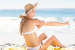 Pretty blonde woman spreading sun tan lotion on her arms Stock Photos