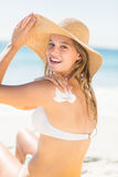 Pretty blonde woman spreading sun tan lotion on her shoulder Royalty Free Stock Photos