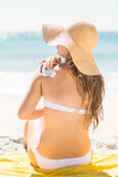 Pretty blonde woman spreading sun tan lotion on her shoulder Royalty Free Stock Photography