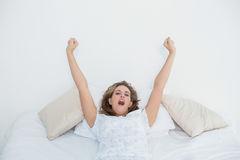 Pretty blonde woman stretching in bed and yawning Royalty Free Stock Images