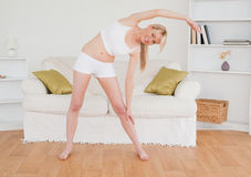 Pretty blonde woman stretching in the living room Stock Images