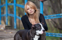 Pretty blonde woman stroking a purebred dog Stock Photo